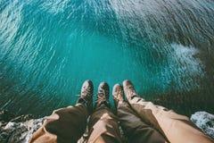 Couplez les pieds au-dessus de la mer sur l'amour de falaise et voyagez Images stock