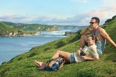 Couplez les randonneurs avec des sacs à dos appréciant le coucher du soleil à la côte de montagne Image libre de droits