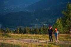 Couplez les randonneurs avec des sacs à dos tenant des mains, marchant dans les montagnes Photo stock