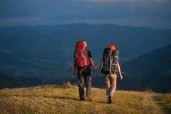 Couplez les randonneurs avec des sacs à dos tenant des mains, marchant dans les montagnes Image stock