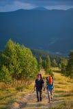 Couplez les randonneurs avec des sacs à dos tenant des mains, marchant dans les montagnes photos libres de droits
