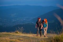 Couplez les randonneurs avec des sacs à dos tenant des mains, marchant dans les montagnes Images libres de droits