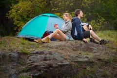 Couplez les randonneurs chez l'homme et la femme sauvages de forêt se reposant avec la tasse Image libre de droits