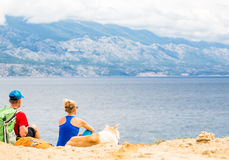 Couplez les randonneurs marchant avec le chien au bord de la mer et aux montagnes Photo stock