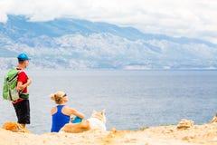 Couplez les randonneurs marchant avec le chien au bord de la mer et aux montagnes Image libre de droits