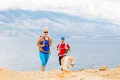 Couplez les randonneurs marchant avec le chien au bord de la mer et aux montagnes Photo libre de droits