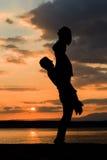 Couplez les silhouettes se tenant au coucher du soleil par la mer, se soulevant Photographie stock libre de droits