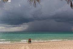 Couplez les supports sur la plage et voyez comment un tsunami vient Image libre de droits