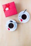 Couplez les tasses avec du café, boîte-cadeau décoré par les coeurs rouges sur la table en bois Image stock