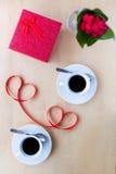Couplez les tasses avec du café, décoré par le ruban sur la table en bois Photographie stock