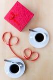 Couplez les tasses avec du café, décoré par le ruban sur la table en bois Images stock