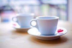 Couplez les tasses avec du café décoré par les coeurs rouges sur la table en bois Images libres de droits