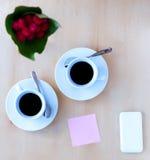 Couplez les tasses avec du café, fleurissez, téléphonez, autocollant sur la table en bois Image libre de droits