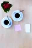 Couplez les tasses avec du café, fleurissez, téléphonez, autocollant sur la table en bois Photo libre de droits