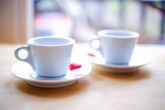 Couplez les tasses avec la décoration par les coeurs rouges sur la table en bois Photo libre de droits