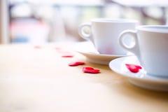 Couplez les tasses avec la décoration par les coeurs rouges sur la table en bois Image libre de droits