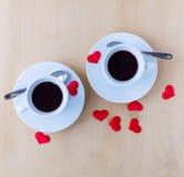 Couplez les tasses avec la décoration par les coeurs rouges sur la table en bois Photographie stock