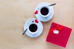 Couplez les tasses avec le boîte-cadeau et les coeurs sur la table en bois Photo libre de droits