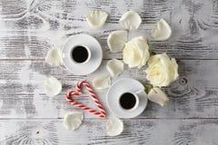 Couplez les tasses blanches avec la décoration par les coeurs rouges sur la table en bois Images stock