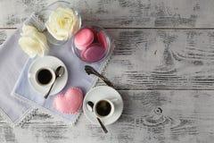 Couplez les tasses blanches avec la décoration par les coeurs rouges sur la table en bois Photographie stock