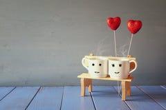 Couplez les tasses de café sur le vieux banc à côté des coeurs rouges Images libres de droits