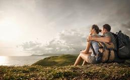 Couplez les touristes avec des sacs à dos appréciant le coucher du soleil sur un bâti Photos libres de droits
