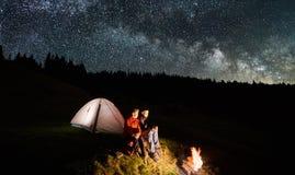 Couplez les touristes près du feu de camp et des tentes sous le ciel nocturne complètement des étoiles et de la manière laiteuse Photographie stock libre de droits