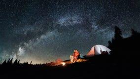 Couplez les touristes près du feu de camp et des tentes sous le ciel nocturne complètement des étoiles et de la manière laiteuse Images stock