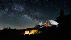 Couplez les touristes près du feu de camp et des tentes sous le ciel nocturne complètement des étoiles et de la manière laiteuse Photo stock