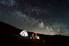 Couplez les touristes près du feu de camp et des tentes sous le ciel nocturne complètement des étoiles et de la manière laiteuse Photo libre de droits