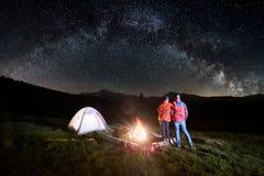 Couplez les touristes près du feu de camp et des tentes sous le ciel nocturne complètement des étoiles et de la manière laiteuse Photos stock