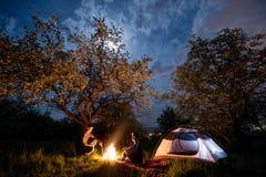 Couplez les touristes s'asseyant à un feu de camp près de la tente sous des arbres et du ciel nocturne avec la lune Camping de nu Photos libres de droits