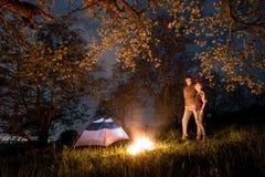 Couplez les touristes se tenant à un feu de camp près de la tente, étreignant et regardant entre eux sous les arbres et le ciel n Photos libres de droits