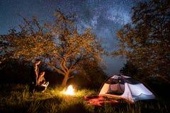 Couplez les touristes se tenant à un feu de camp près de la tente sous des arbres et du beau ciel nocturne complètement des étoil Photographie stock