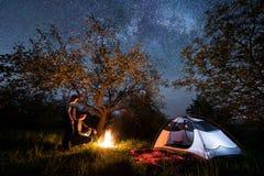 Couplez les touristes se tenant à un feu de camp près de la tente sous des arbres et du beau ciel nocturne complètement des étoil Images libres de droits