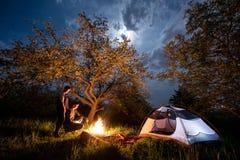 Couplez les touristes se tenant à un feu de camp près de la tente sous des arbres et du ciel nocturne avec la lune Camping de nui Photographie stock libre de droits