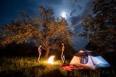 Couplez les touristes se tenant à un feu de camp près de la tente sous des arbres et du ciel nocturne avec la lune Camping de nui Photos stock