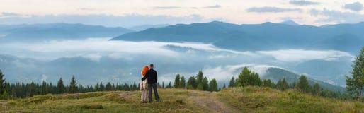 Couplez les touristes se tenant sur une colline appréciant une brume de matin Photographie stock