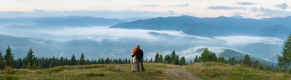 Couplez les touristes se tenant sur une colline appréciant une brume de matin Image libre de droits