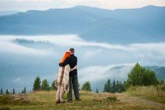 Couplez les touristes se tenant sur une colline appréciant une brume de matin Image stock