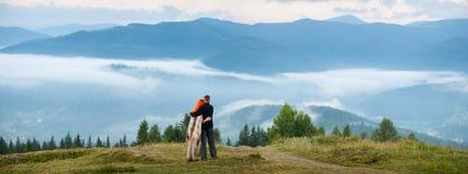 Couplez les touristes se tenant sur une colline appréciant une brume de matin Photographie stock libre de droits