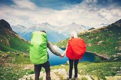Couplez les voyageurs d'homme et de femme avec le sac à dos tenant l'alpinisme de mains Photos stock