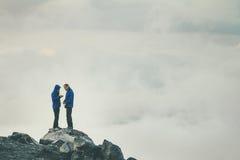 Couplez les voyageurs dans l'amour se tenant sur la falaise ensemble Photos stock