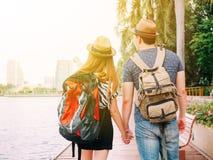 Couplez les voyageurs marchant et tenant le voyage de mains ensemble - de Photos stock