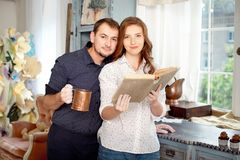 Couplez lire un livre des recettes pour faire cuire quelques plats Photo stock