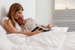 Couplez lire un livre se situant dans le lit Photo stock
