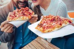 Couplez manger de la pizza dehors dans un café, fermez-vous  Image libre de droits