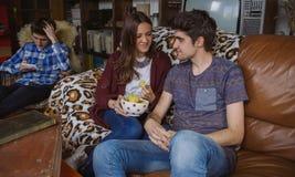 Couplez manger des puces sur un regard de sofa et d'ami Photos stock