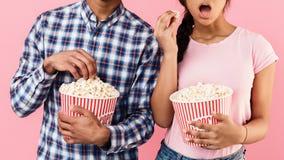 Couplez manger du maïs éclaté, film de observation, fond rose image libre de droits
