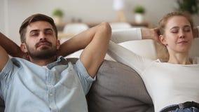Couplez mettre des mains derrière la tête détendant sur le sofa à la maison banque de vidéos